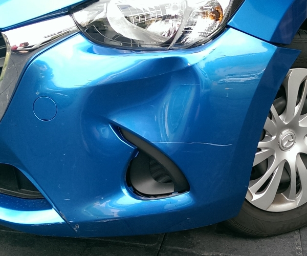 Mazda 2 bumper dent, before bumper repairs by All About Bumpers