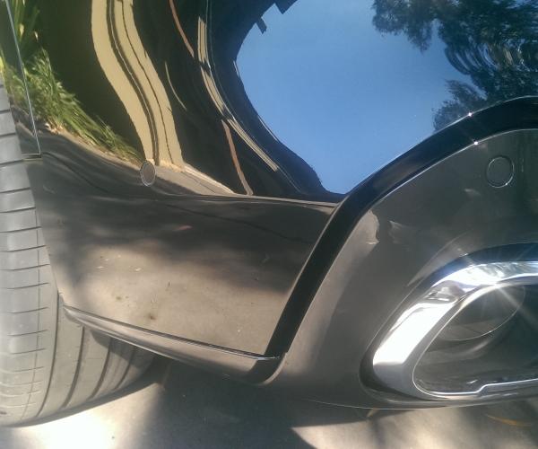 Black BMW X5 rear bumper paint scratch repair, after repair.