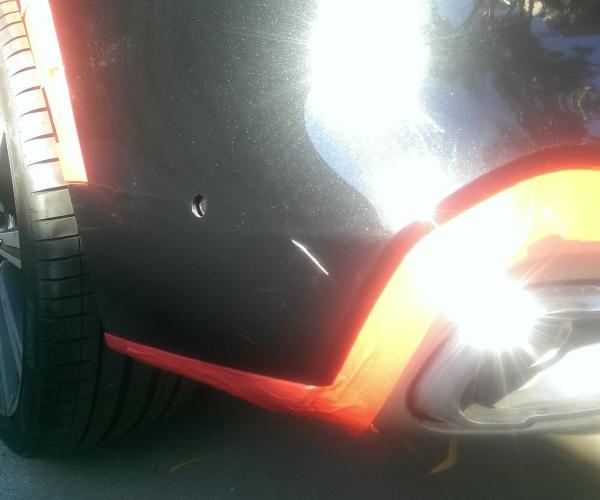 Black BMW X5 rear bumper paint scratch repair, before repair.