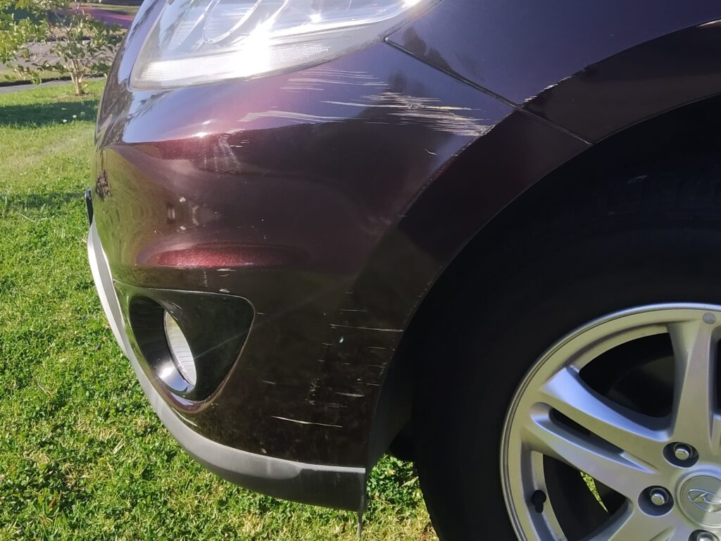 Front bumper paint damage on a Hyundai Santa Fe, Bumper is scraped on the left hand side, before repaired by All About Bumpers